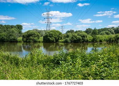 Summer landscape - High-voltage transmission lines pass over a pond surrounded by trees