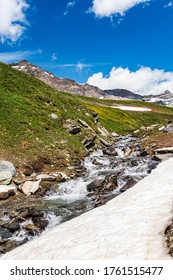 Summer landscape in italian  mountains. Meadow, nature, little waterfall and a beautiful cloudy sky.