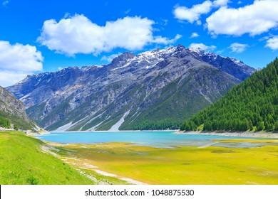 Summer landscape at Lago di Livigno or Lago del Gallo, a reservoir lake in the Livigno valley, Grisons, Lombardy, Italy.