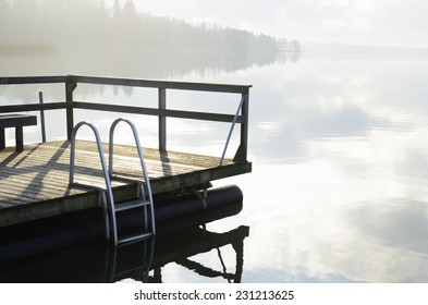 summer landscape, lake and wooden jetty in fog
