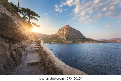 Summer landscape with mountain path, rocks, trees growing out of the cliff, blue sea and blue sky with clouds at sunset. Nature background. Beautiful trail through the mountain. Travel in Crimea.