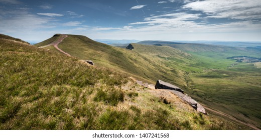 Summer landscape of mountain Pen Y Fan, Brecon Beacons, Wales, UK, seen from a walking trail to the top, with saturated green grassland and rocky outcrops, including a gravel path and backed up by a b