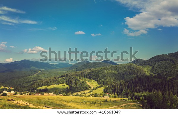 Summer landscape in mountains and the dark blue sky with clouds. Retro color.