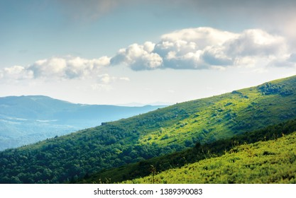 summer landscape in mountains. green grassy meadows on top of the ridge. blue sky with white clouds