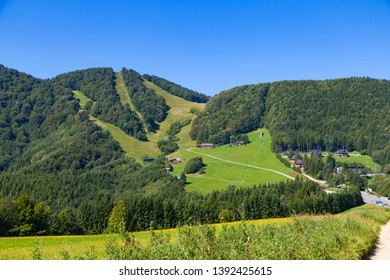 Summer landscape in the mountains. View from above  the tops of the mountains, covered with forest. Mountain village. Slovakia,  Trencin region, near Klachno. Tourist destination, tourism, hiking.