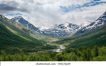 Summer landscape of norwegian mountains with snow on it's peaks and green forest below. River from melted ice is running between the mountain slopes. Norway.