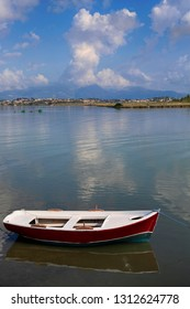 Summer landscape off the coast of Corfu island in Greece with a fishing boat in calm sea water, beautiful cloudy sky and mountains in the background
