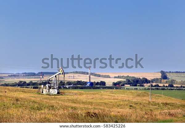 summer landscape oil pumps in a field on a clear sunny day