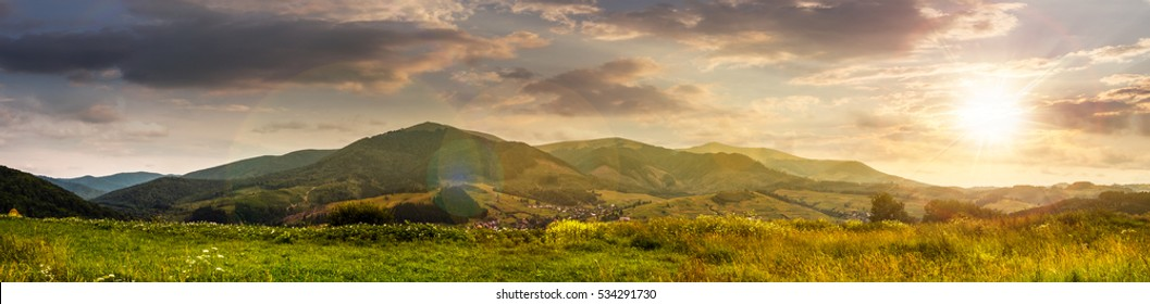 Summer landscape panoramic image of rural fields in mountains under cloudy sky in evening light