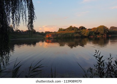 summer landscape pink and orange sunset over the tranquil river and trees on the shore