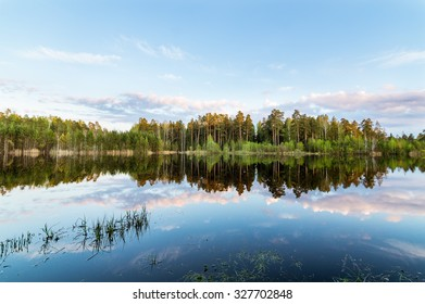 summer landscape at a pond with reflection in water, forest, Russia, the Urals