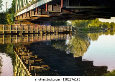 Summer landscape of reflections in water of the River Cam under the railway bridge in East Chesterton, Cambridge. With wooden walkway into countryside beyond.