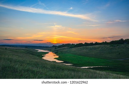 Summer landscape with river flowing betweeen the green hills on a background of colorful sunset sky.Tula region,Russia.