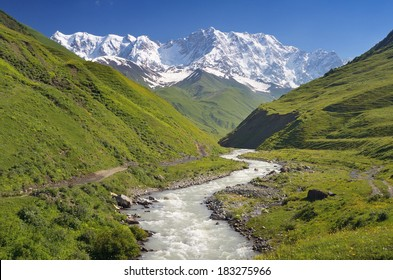 Summer landscape with river and mountain snow. Peak Shkhara Zemo Svaneti, Georgia. The main Caucasian ridge