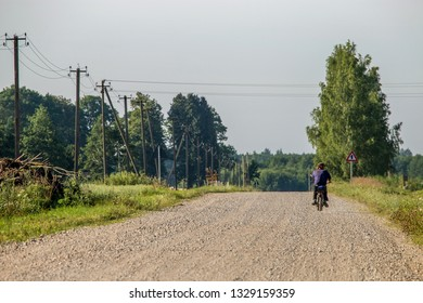 Summer landscape with road, trees and blue sky. Man ride to the moped on countryside road. Rural road, cornfield, wood and cloudy blue sky. Classic rural landscape in Latvia.