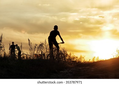 summer landscape silhouette of a boy on a bicycle, with rolling hills on the background of golden sunset