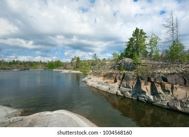 Summer landscape. A small bay among the stone banks, dry and green trees on the rocks. Blue sky with clouds. Russia, Finland, Karelia, Lake Ladoga