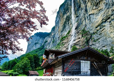 Summer landscape with the Staubbach waterfall in Lauterbrunnen at the background, a typical wooden house with some vintage skiis on the wall on the right corner and a tree with red leaves on the left.