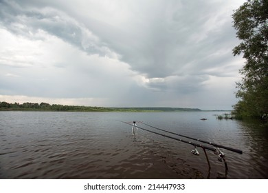 summer landscape storm clouds over the river and spinning on a stand near the shore