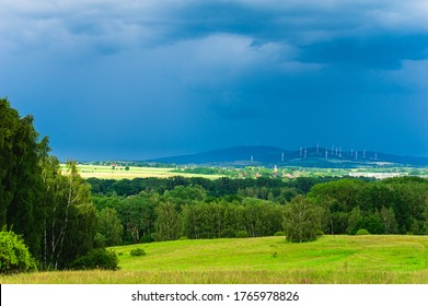 summer landscape with trees and windpark and storm clouds