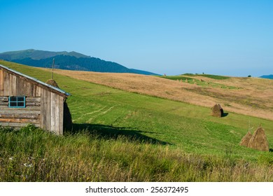 Summer landscape in the Ukrainian Carpathian Mountains with the wooden shed in the foreground,