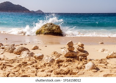 Summer landscape, waves with brakes break on a stone, a cairn of stones in the sand, Kaputas beach, Turkey.