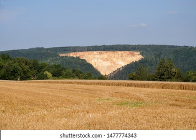 summer landscape with wheat field in swabian alb with limestone quarry in background