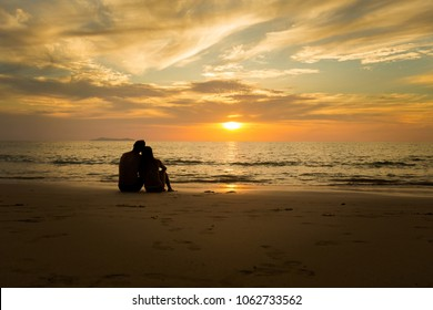 Summer landscape with young caucasian tourist couple watching golden sunset on tropical koh Kradan island in Thailand. Holiday photos taken in paradise scene during honeymoon.
