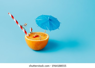 Summer layout with miniature people surfing and swimming on orange against vibrant blue background. Creative vacation concept. Minimal tropical cocktail, exotic juice bar or sea activity banner.