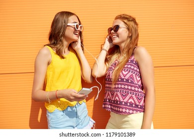 summer, leisure and technology concept - smiling teenage girls in sunglasses and earphones listening to music from smartphone outdoors