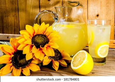 Summer lemonade with lemon slices, pitcher, and sunflowers on wood bench.