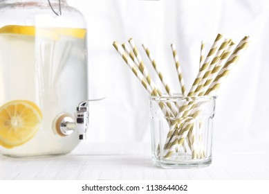Summer Lemonade Still Life: A lemonade pitcher with a glass of drinking straws in front of a kitchen window. Focus is on the straws, horizontal orientation.