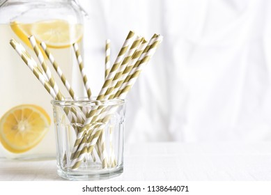 Summer Lemonade Still Life: A lemonade pitcher with a glass of drinking straws in front of a kitchen window. Horizontal format with copy space. Focus is on straws.
