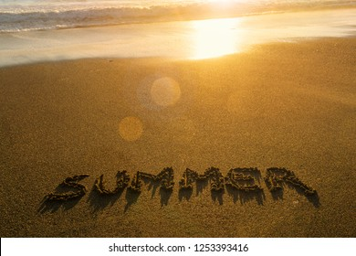 Summer in letters written in the sand at sunset, holidays by the sea concept with copy space.