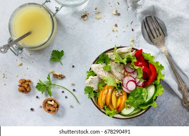 Summer lettuce with salad dressing vinaigrette. Salad with chicken, fresh vegetables, walnuts and greens on a gray stone background or slate. Top view.