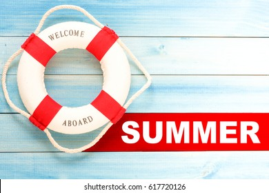 Summer and lifebuoy with Welcome aboard phrase and summer time text on wooden background