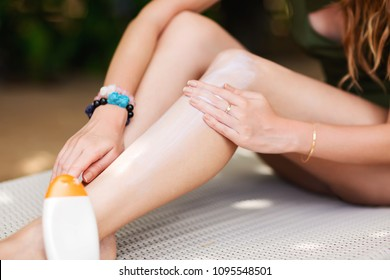Summer lifestyle close up image of young pretty woman smearing the suntan cream on legs for protect skin healthy. Lying on the sunbed on the tropical beach. Wearing stylish bikini. Sun protect concept