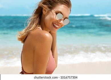 Summer lifestyle concept. Tanned slim happy beautiful female with bare shoulders sunbathes at sandy beach, enjoys ideal place for recreation and real paradise, relaxes at ocean shore outdoor.