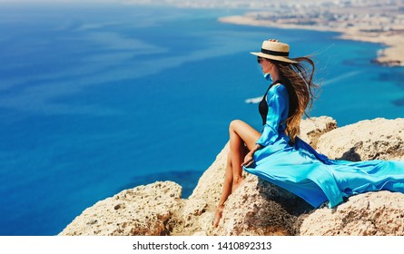 Summer lifestyle fashion image of happy stunning woman sitting on the cliff above the sea. Enjoying life and looking at the sea. Turquoise sea background. Wearing stylish dress, straw hat, sunglasses