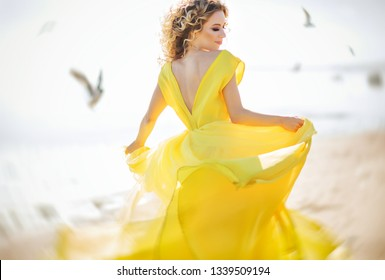 Summer lifestyle fashion portrait of stunning happy blonde woman running on the beach. Wearing long yellow dress. Perfect make up and curls. Evening dress. Romantic mood. Enjoying sunlights. Sunny day