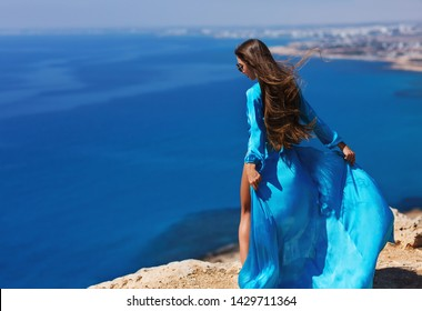 Summer lifestyle fashion portrait of stunning woman posing on the cliff above the sea. Turquoise sea background. Wearing stylish dress. Perfect long hair. Dress and hair flying in the wind. Freedom