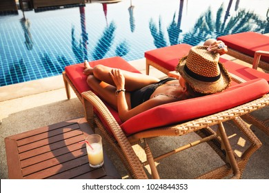 Summer lifestyle fashion portrait of young stunning tanned woman. Enjoying life on the sunbed near the pool. Wearing stylish straw hat and black bikini. Sunbathing. Holiday and travelling concept