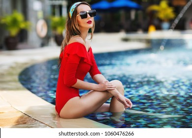 Summer lifestyle fashion portrait of young stunning blonde girl sitting in the pool. Sunbathing and enjoying life. Wearing stylish square shape sunglasses, red swimsuit with sleeves. Red lips. Sunny