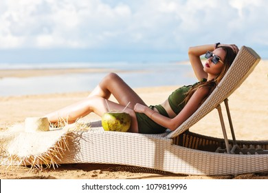 Summer lifestyle fashion portrait of young stunning woman drinking young coconut on the beach of the tropical island. Enjoying life on the beach chaise. Wearing stylish sunglasses, bikini. Sunbathing.