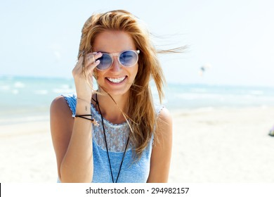 Summer lifestyle happy smiling portrait of pretty young woman blonde fashion having fun on the beach on tropic island in sunglasses