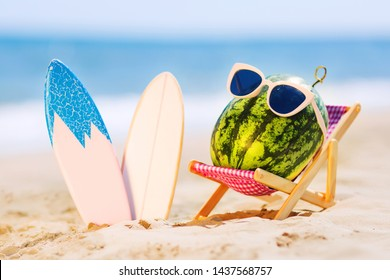 Summer lifestyle image of attractive watermelon surfer lying on sunbed on the sand against turquoise sea. Wearing stylish sunglasses. Surfstyle. Tropical summer vacation concept. Sunbathing on beach