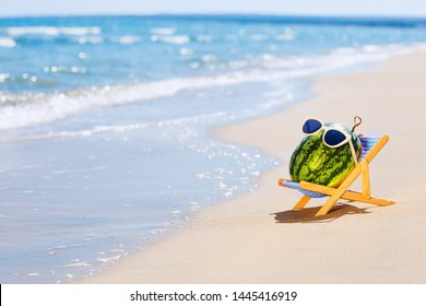 Summer lifestyle image of attractive watermelon lying on sunbed on the sand against turquoise sea. Wearing stylish sunglasses with white frame. Tropical summer vacation concept. Sunbathing on beach