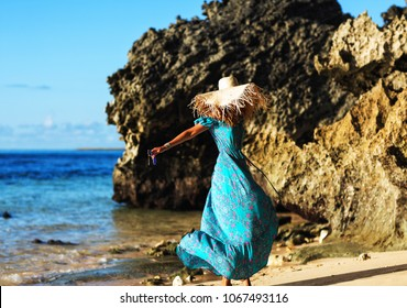 Summer lifestyle image of happy stunning woman whirling on the tropical beach. Dancing and enjoying life in paradise. Sea and rocks background. Wearing stylish long summer blue dress, straw hat. Happy