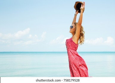 Summer lifestyle image of happy stunning woman soaring on the tropical beach. Jumping and enjoying life in paradise. Sea background. Wearing stylish long red wine dress, sunglasses. Happiness concept