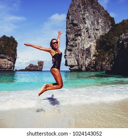 Summer lifestyle image of happy young tanned woman jumping carefree on the tropical beach. Enjoying sun. Wearing stylish mirrored sunglasses, black bikini. Sunbathing. Freedom and happiness concept.